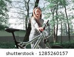 young woman with a bicycle in... | Shutterstock . vector #1285260157