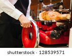Shopkeeper cutting ham slices in a grocery store - stock photo
