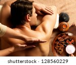 masseur doing massage on man... | Shutterstock . vector #128560229