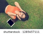 asian woman listening music... | Shutterstock . vector #1285657111