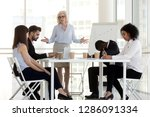 Small photo of Angry dissatisfied company owner or team leader mature businesswoman scold young diverse multiracial incompetent workers. Multi-ethnic employees feel guilty made mistake which cause serious losses