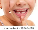 Child pointing to missing teeth, pulled out with a string - closeup on mouth - stock photo