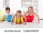 Happy people exercising - woman and kids with large gymnastic balls - stock photo