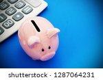 piggy bank and calculator on... | Shutterstock . vector #1287064231