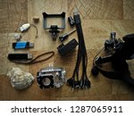 Action camera, aqua box and other photo video accessories are on the table on a wooden background, isolated object.