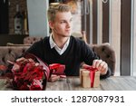 a young man sits in a... | Shutterstock . vector #1287087931