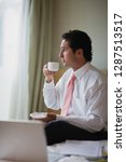 young businessman drinking from ... | Shutterstock . vector #1287513517