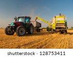 Постер, плакат: Modern combine harvester unloading