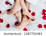 Stock photo partial view of barefoot couple lying on soft white bedding with red petals 1287702481