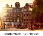 Stock photo sunset in amsterdam netherlands many bikes on a typical little bridge over a canal in jordaan 128781959