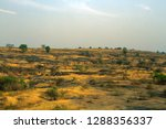 Small photo of India, Aurangabad - 28 March 2018: Poor Indian fields among bush rocky terrain, fragmental soil, shirttail ranch, parcels. Yellow winter fields after harvest. Yellow agricultural landscape