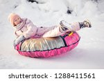 cute kid riding on tube at... | Shutterstock . vector #1288411561