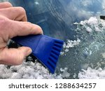 cold hand with blue ice scraper ...   Shutterstock . vector #1288634257