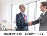 smiling businessmen shaking... | Shutterstock . vector #1288944421