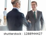 smiling businessman shaking... | Shutterstock . vector #1288944427