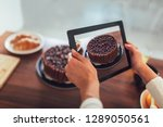Stock photo blogger taking picture of cake to upload on website 1289050561