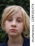 Small photo of Portrait of a pale unhappy tired listless young blond girl