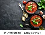 Small photo of Traditional spanish cold tomato soup gazpacho in a bowl over black slate, stone or concrete background.Top view with copy space.