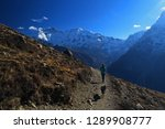 Stock photo female hiker with a dog walking from the ice lake a popular acclimatization trip on the annapurna 1289908777