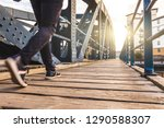 man walking over a bridge at... | Shutterstock . vector #1290588307