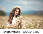 Small photo of Beautiful young girl with flowers enjoying in chamomile field. Carefree happy brunette woman with chaplet on healthy wavy hair having fun outdoor in nature. People freedom style.