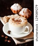 Cup of coffee with chocolate, coffee beans and muffins on a dark background. - stock photo
