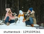 Couple Making Snowman Outdoors. ...
