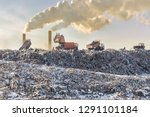 Dump trucks unloading garbage over vast landfill. Smoking industrial stacks on background. Environmental pollution. Outdated method of waste disposal. Survival of times past