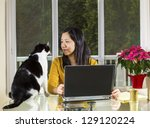 Stock photo mature asian woman looking into family cat face while working at home with notebook computer on 129120224