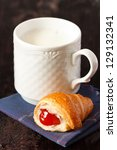 Mug of fresh milk and croissant with jam for breakfast. - stock photo