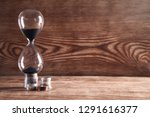 coins and hourglass on a wooden ... | Shutterstock . vector #1291616377