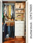 Small photo of Clothes hung neatly in organized closet at home
