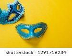 Table top view aerial image of beautiful colorful carnival season or photo booth prop Mardi Gras background.Flat lay object blue mask on modern yellow wallpaper.Free space for creative design mock