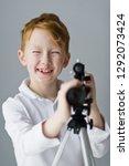 kid looks through a telescope... | Shutterstock . vector #1292073424
