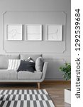 Small photo of Real photo of a grey living room interior with triptych on a wall, couch and striped rug