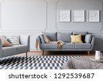 Small photo of Real photo of a spacious living room interior with to sofa, triptych and striped carpet