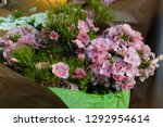 Small photo of Minutisa bouquet wrapped in Green paper. Minutiae flower for sale in a florist shop