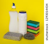 Small photo of Dishwashing liquid, powder and three types of sponges of different hardness on a yellow background. Kitchen detergent. Household chemicals. Household chores.