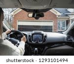 Small photo of Unidentified young lady is reversing the car from garage on the drive way using rear camera while looking at the screen.