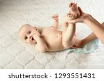 mother putting diaper on her... | Shutterstock . vector #1293551431