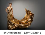Woman Gold Dress, Fashion Model in Long Waving Fluttering Gown, Young Girl Beauty Studio Portrait