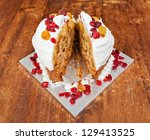 Christmas cake with cream and red berries cut in two slices - stock photo
