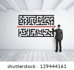 Stock photo businessman drawing maze on white wall 129444161