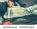 Auto Technician Spotting Problem. Caucasian Mechanic in His 30s Looking Under the Car Hood. Automotive Concept. - stock photo