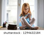 pretty little girl using a... | Shutterstock . vector #1294632184