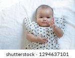 asian baby in black dot shirt... | Shutterstock . vector #1294637101