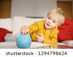 little boy putting coin into... | Shutterstock . vector #1294798624