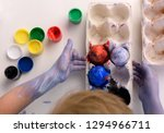 the boy is painting easter eggs.... | Shutterstock . vector #1294966711