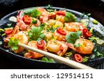 Chopsticks and fried shrimp with herbs - stock photo