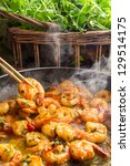 Hot shrimp fried in a pan with butter and herbs - stock photo